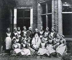 An old Florence Nightingale surrounded by members of staff and nurses in education.